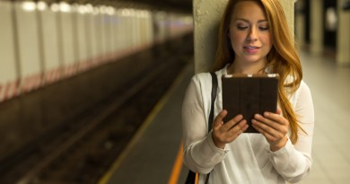 Young caucasian woman in city using tablet pc computer at subway platform