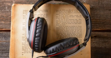 Headphones on the old book. Concept of listening to audiobooks.